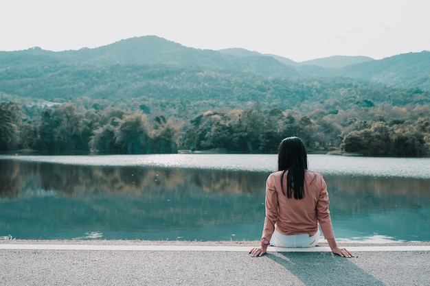 ヒップスターの女性は、コピースペースとマウンテンの背景に公園に一人で座っています。