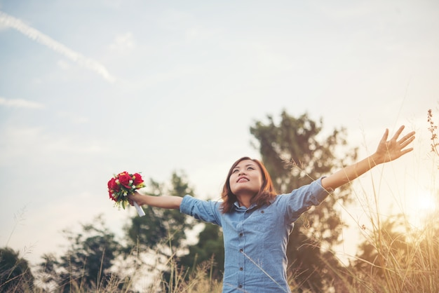 Hipster woman smile enjoy with fresh air raising arm in summer field, vintage tone filter.