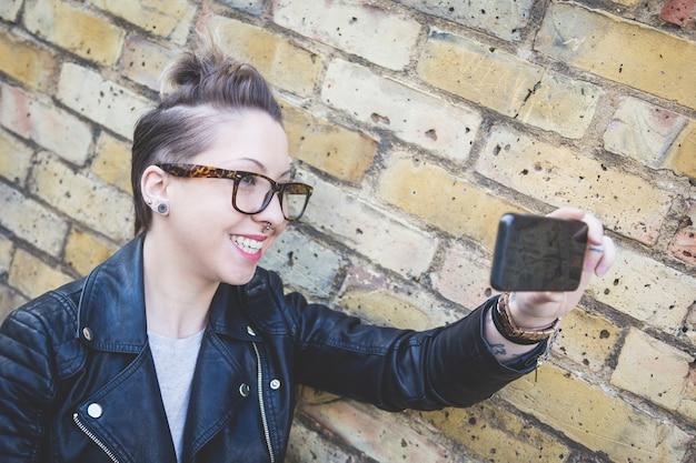 Женщина битника принимая selfie против кирпичной стены в лондоне.