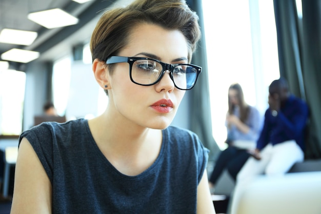Hipster woman use laptop huge loft studio.student researching process work.young business team working creative startup modern office.analyze market stock,new strategy.blurred,film effect.