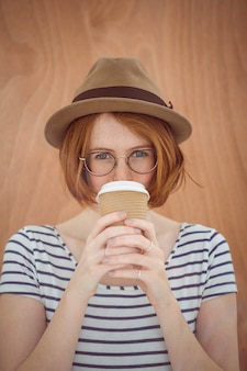 Hipster woman with red hair drinking coffee