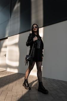검은색 유행 옷에 선글라스를 낀 힙스터 여성:가죽 재킷, 운동복, 타이츠, 핸드백이 있는 세련된 부츠는 햇빛 아래 도시를 걷습니다.
