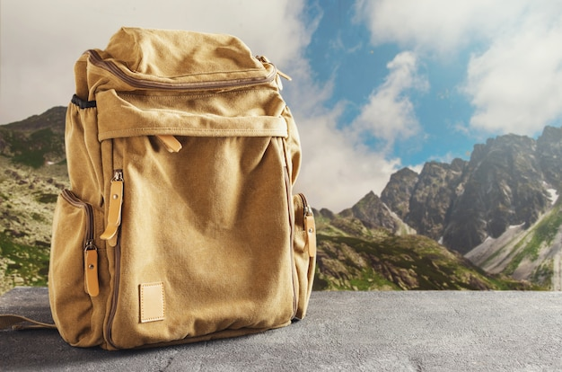 Hipster yellow backpack on the table against the mountains. hiking in the mountains concept