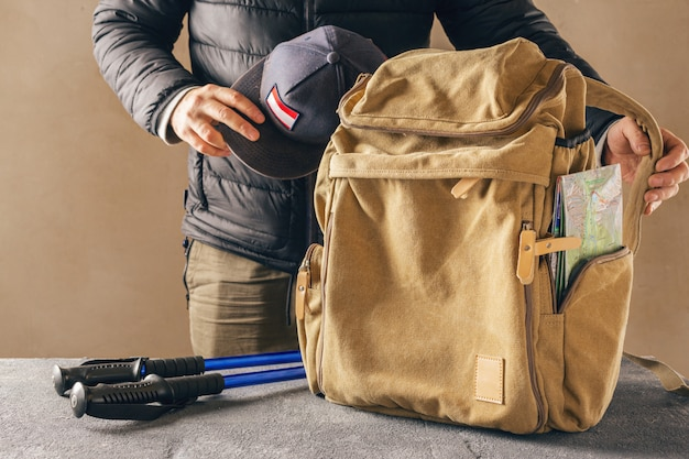 Hipster yellow backpack with map and trekking hiking stick. male traveler preparing for a hike in the mountains