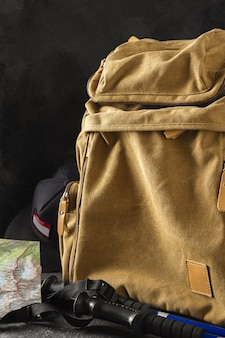 Hipster yellow backpack with map and walking poles hiking in the mountains concept