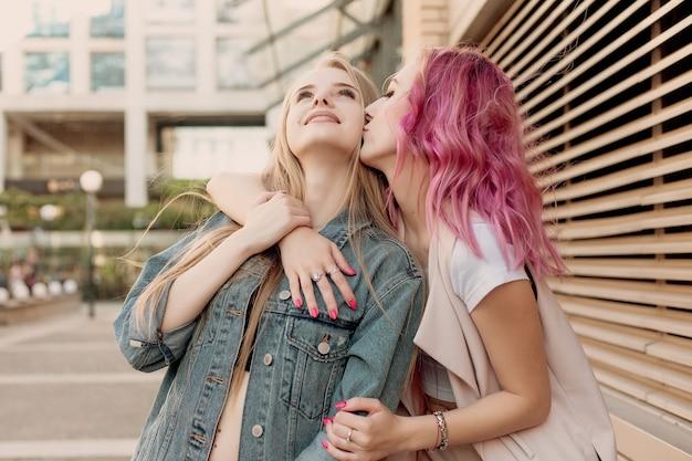 도시에서 어울리면서 껴안은 힙스터 젊은 성인 친구들. 평온한 휴가 생활을 즐기며 웃고 걷는 두 젊은 여성
