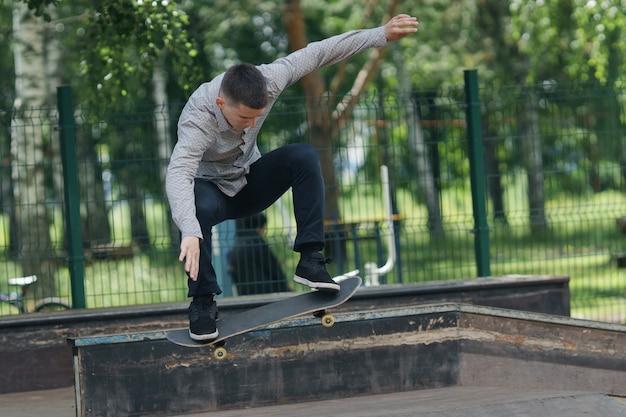 流行に敏感な-日当たりの良い夏の公園のヘッジでジーンズとシャツのスケートボードの若いかわいい男