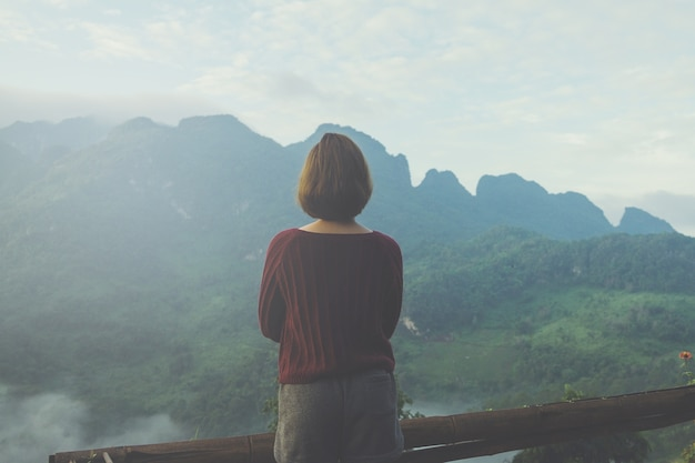 Hipster young female enjoying on peak of foggy mountain, tourism at thailand.