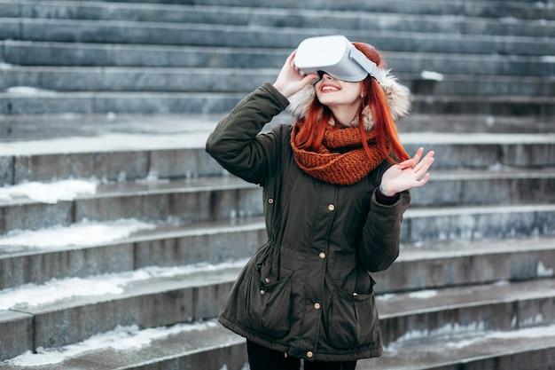 流行に敏感な少女は、屋外のモダンなvrメガネに接続されたスマートフォンでバーチャルリアリティモバイルゲームアプリを再生します