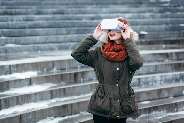 Hipster 어린 소녀는 현대 vr 안경 야외에 연결된 스마트 폰에서 가상 현실 모바일 게임 앱을 재생합니다.