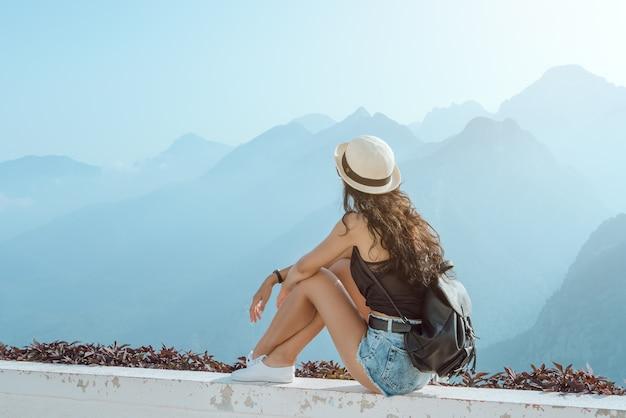 Маленькая девочка битника с рюкзаком, наслаждаясь закатом на пике горы. туристический путешественник сидит на