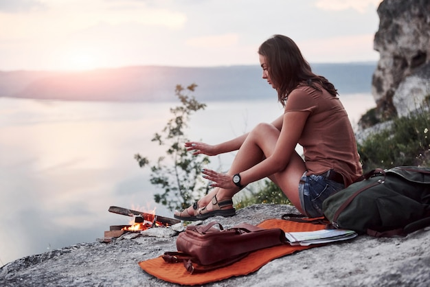 Hipster young girl with backpack enjoying sunset on peak of rock mountain. tourist traveler on background view mockup