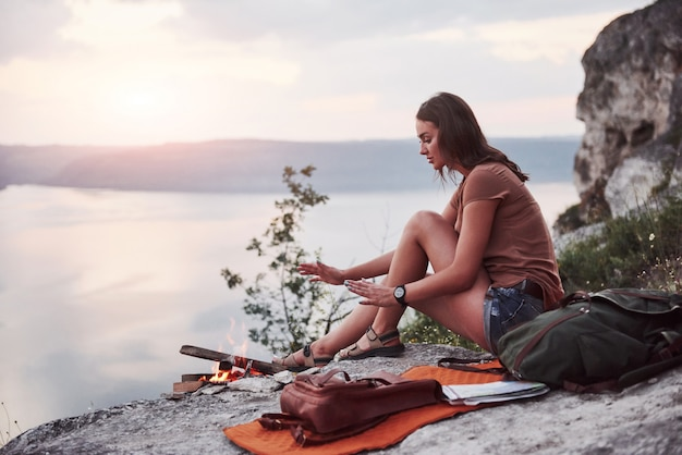 Hipster young girl with backpack enjoying sunset on peak of rock mountain.