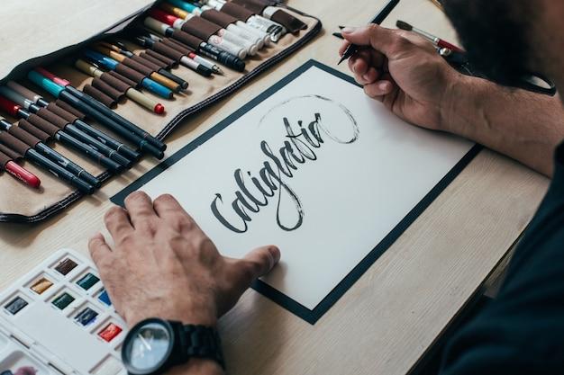 Молодой хипстерский художник-иллюстратор в простой черной футболке создает аутентичный и уникальный рисунок ручной надписи в своей яркой индустриальной студии