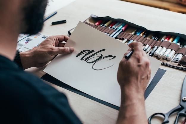 검은 색 단순한 티셔츠의 hipster 젊은 일러스트 레이터 아티스트가 밝은 산업 스튜디오에서 정통하고 독특한 핸드 레터링 드로잉을 만듭니다.