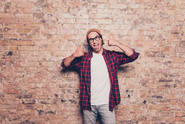 Битник молодой человек обманывает и показывает язык и палец вверх возле кирпичной стены