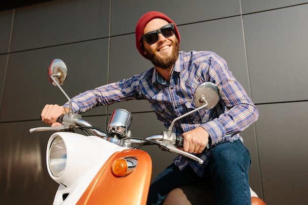 Hipster young  man in helmet is riding on yellow retro scooter in town