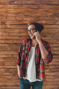 電話で話している帽子と眼鏡の流行に敏感な若い男