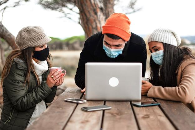 Хипстерский молодой человек использует алюминиевый блокнот на деревянном столе на открытом воздухе со своими двумя подругами в защитной маске от коронавируса