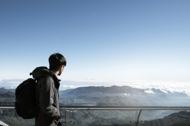 Hipster young man with backpack enjoying on peak of foggy mountain, tourism at vietnam.