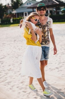 流行に敏感な若いスタイリッシュな流行に敏感なカップルの愛のウォーキングと熱帯のビーチで犬と遊ぶ