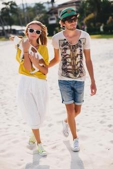 Хипстерская молодая стильная хипстерская влюбленная пара гуляет, играя собаку, щенок джек рассел на тропическом пляже, белый песок, крутой наряд, романтическое настроение, весело, солнечный, мужчина женщина вместе, отпуск