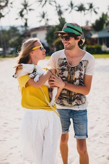 Hipster young stylish hipster couple in love walking playing dog puppy jack russell in tropical beach, white sand, cool outfit, romantic mood, having fun, sunny, man woman together, vacation