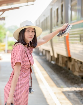 Hipster young traveler waiting train at station,