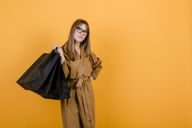 Hipster young woman in glasses and fall trench coat with black shopping bags isolated over yellow