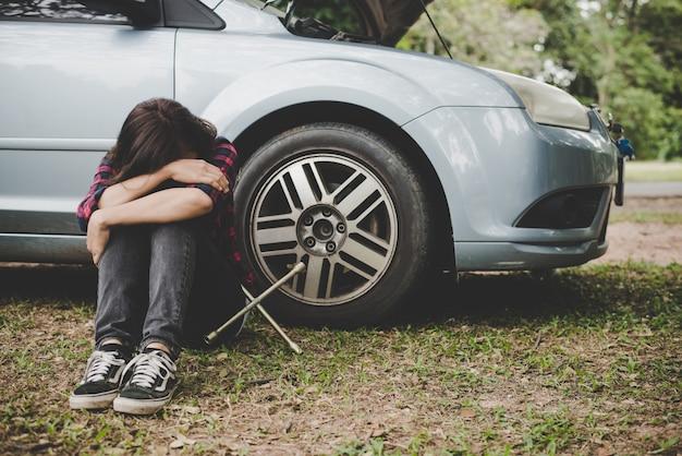 彼女の車の後ろに彼女の車に座って道路の側で彼女の車が壊れた後、道端の援助を待っている若いhipster女性。