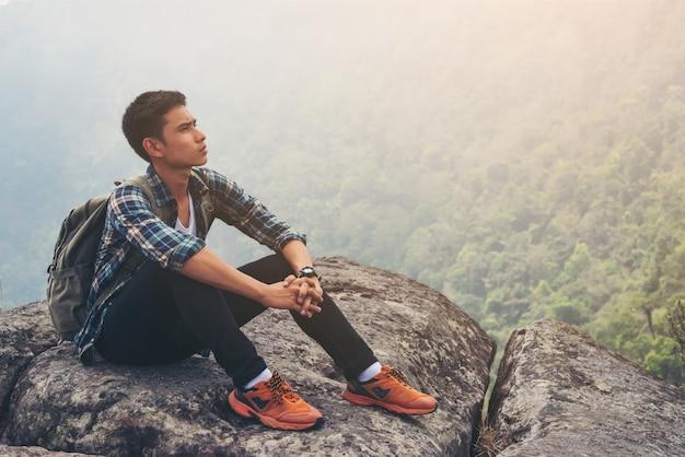 若いhipster男は山頂で休息を取る。旅行のライフスタイルのコンセプト。