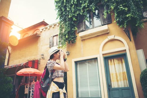 若いhipsterの女性のバックパックは、都市の写真を撮って旅行しています。