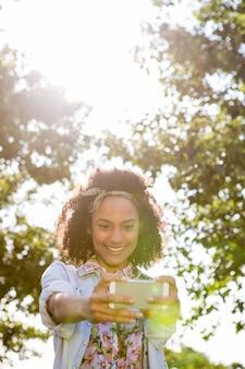 夏の日に彼女のスマートフォンを使用してかなりhipster