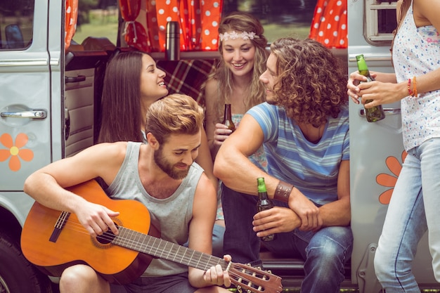 夏の日にフェスティバルでキャンパーバンのhipsterの友達