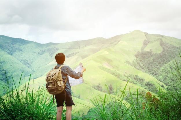 Hipster путешественник человек, держащий карту в горах с потрясающим видом