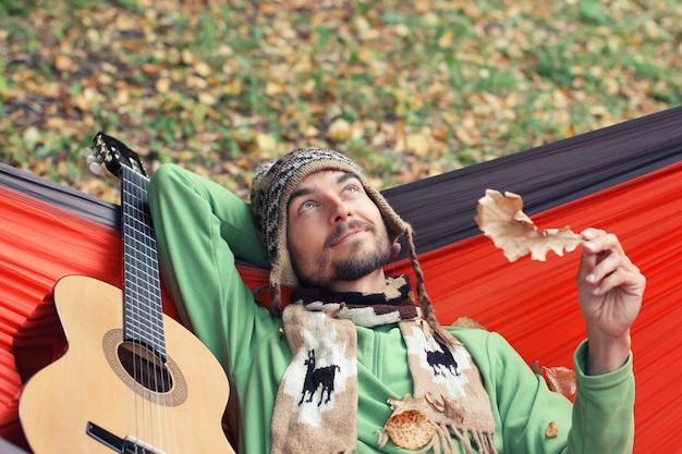 ギターと若いhipster男は、秋の森のハンモックでリラックスします。秋の気分のコンセプト。