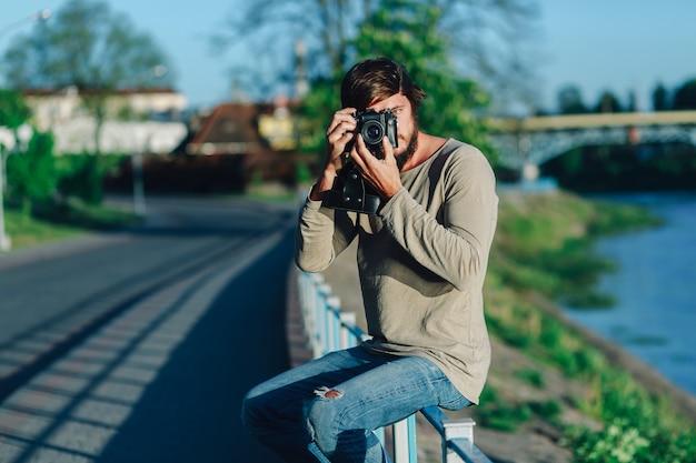 Hipster молодой человек снял фотографию с него пленочной камерой на улице публике