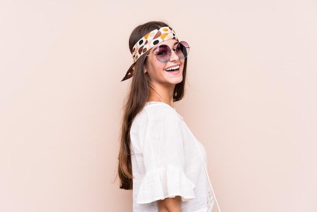 Изолированная женщина молодого hipter кавказская смотрит в сторону усмехаясь, жизнерадостный и приятный.