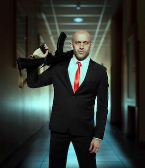 Наемный убийца в костюме и красном галстуке держит в руках автомат.