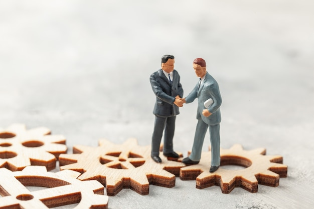 Hiring staff. selection of the leader of the manager for the company. businessmen in suits shake hands on gears as a symbol of business processes in the company