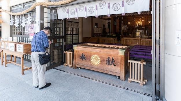 広島、日本-2016年9月:原爆投下によって破壊され、広島城の範囲内で再建された広島五国神社で祈る男性日本人