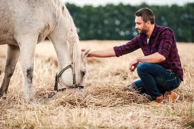 彼の親友。屋外に座って馬に触れる若い農家の側面図