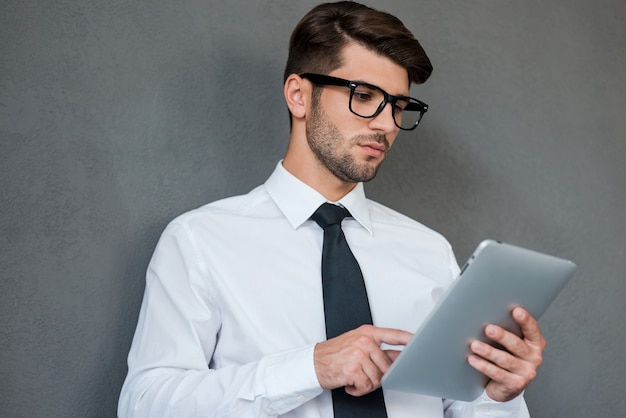 Его партнер по цифровому бизнесу. уверенный молодой человек в рубашке и галстуке, работающий на цифровом планшете