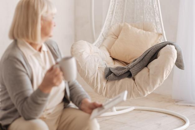 Его любимое место. селективный фокус пустого кресла, стоящего в комнате с лежащим на нем вязаным жакетом