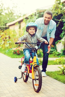 彼の最初の乗り物。自転車に乗って、父が彼を助けている間笑顔