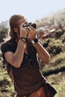 彼の情熱。ビューを撮影するカジュアルな服装の若い男
