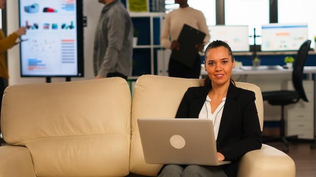 さまざまな同僚がバックグラウンドで作業している間、コンピューターで入力しているソファに座ってカメラに微笑んでいるヒスパニック系ビジネスウーマン。現代のオフィスでスタートアップの財務報告を分析する多民族の同僚