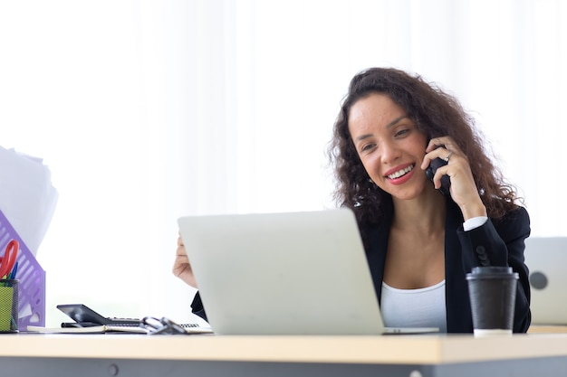 Hispanic business woman talking on mobile phone busy working laptop computer at office. drink coffee