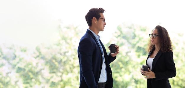 現代のホームオフィスで話したりコーヒーを飲んだりして休んでいるヒスパニックの実業家や実業家。成功するビジネスマンの専門家チーム。