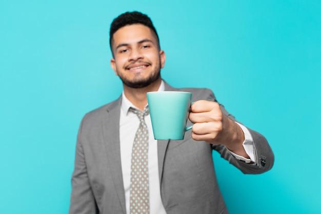 ヒスパニックの実業家の幸せな表現とコーヒーマグカップを保持しています